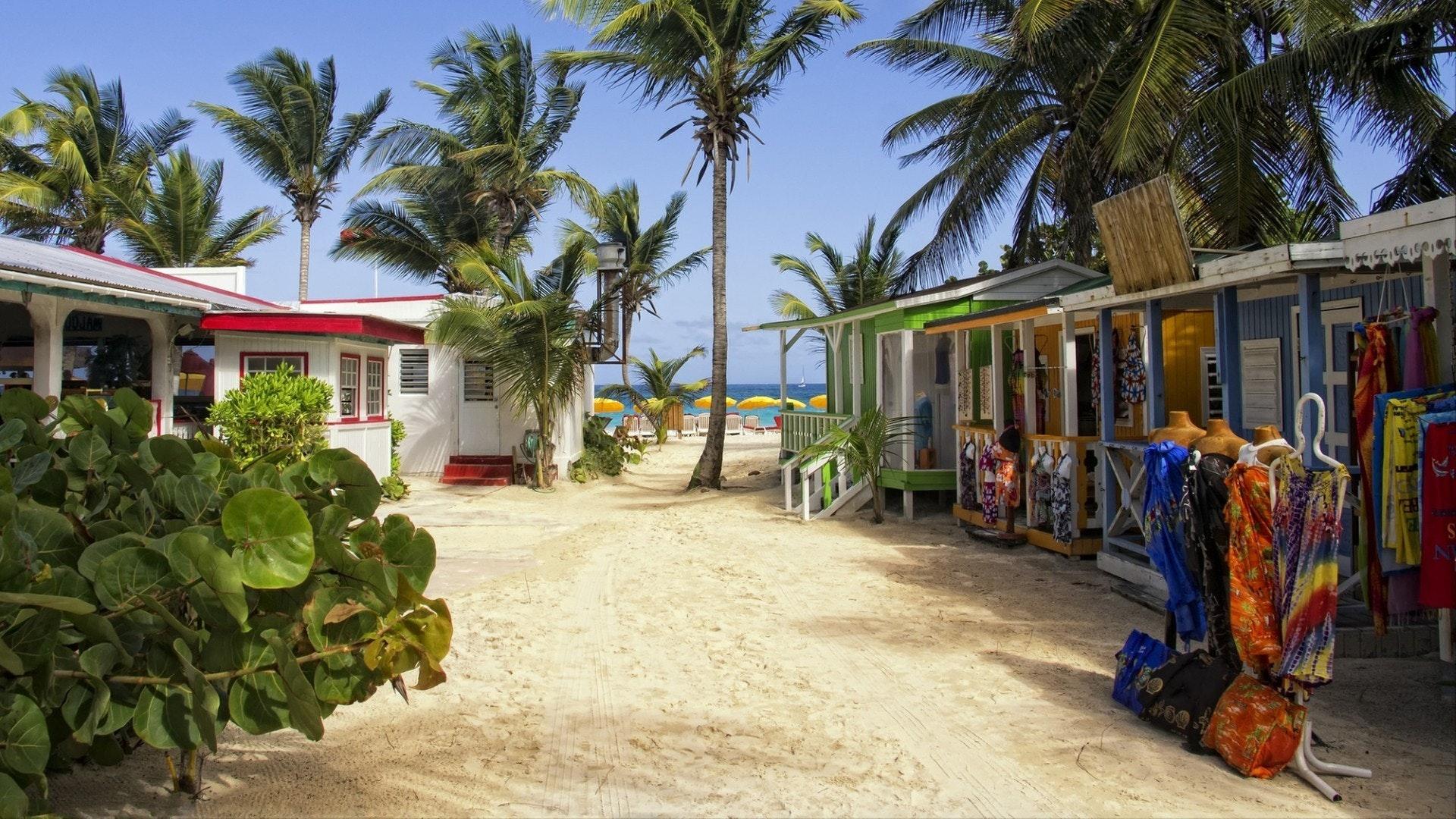 Une rue pleine de vendeurs de rue menant à une plage sur une île des Caraïbes