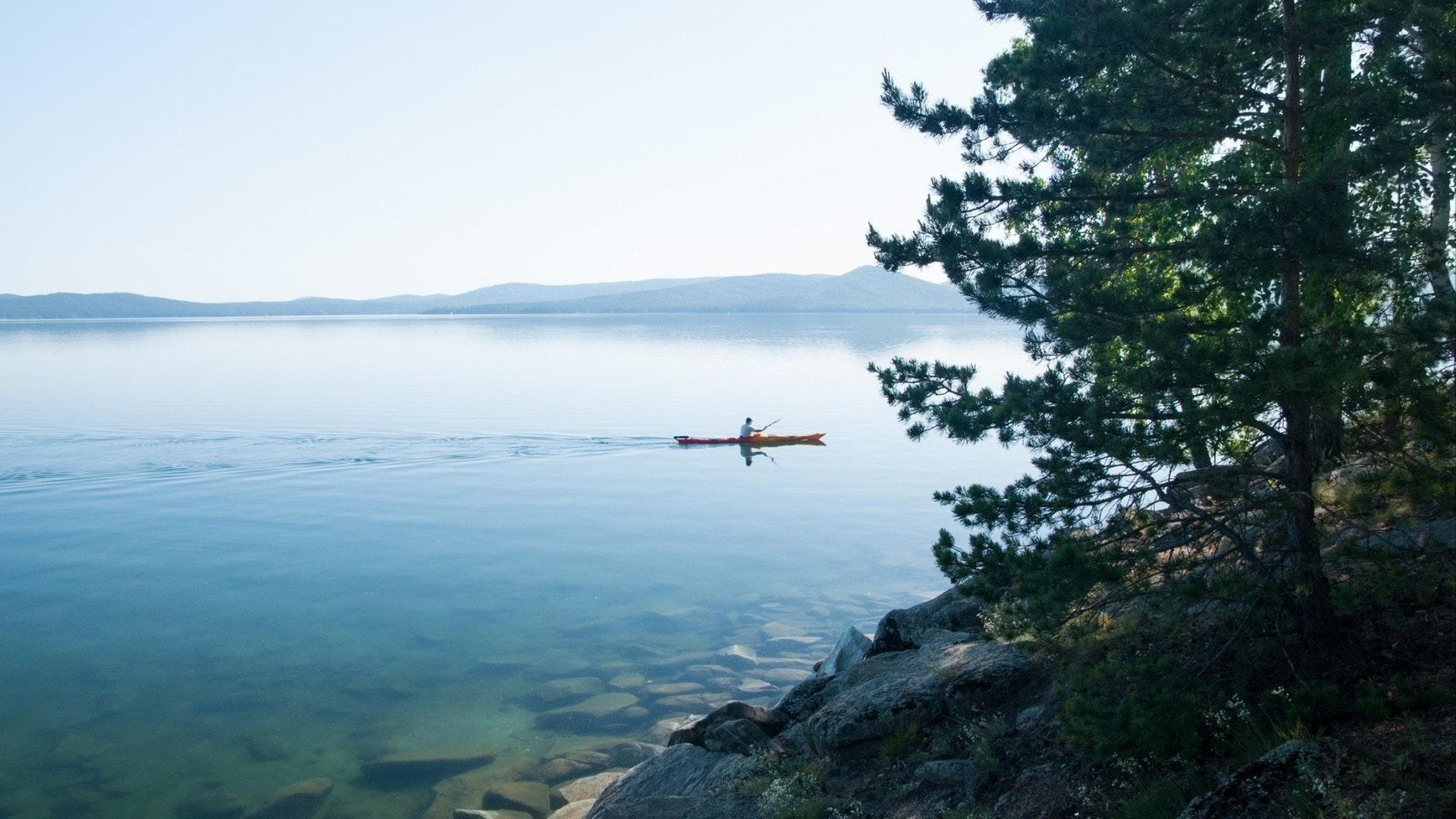 Lago Turgoyak no início do verão com pessoa irreconhecível em canoa