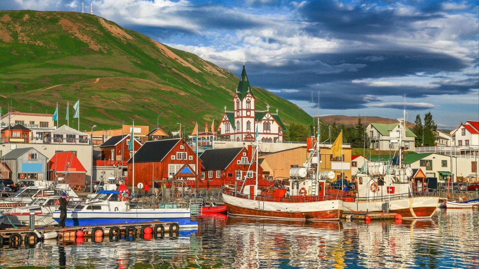 Belle vue sur la ville historique de Husavik avec des maisons colorées traditionnelles et des bateaux de pêche traditionnels