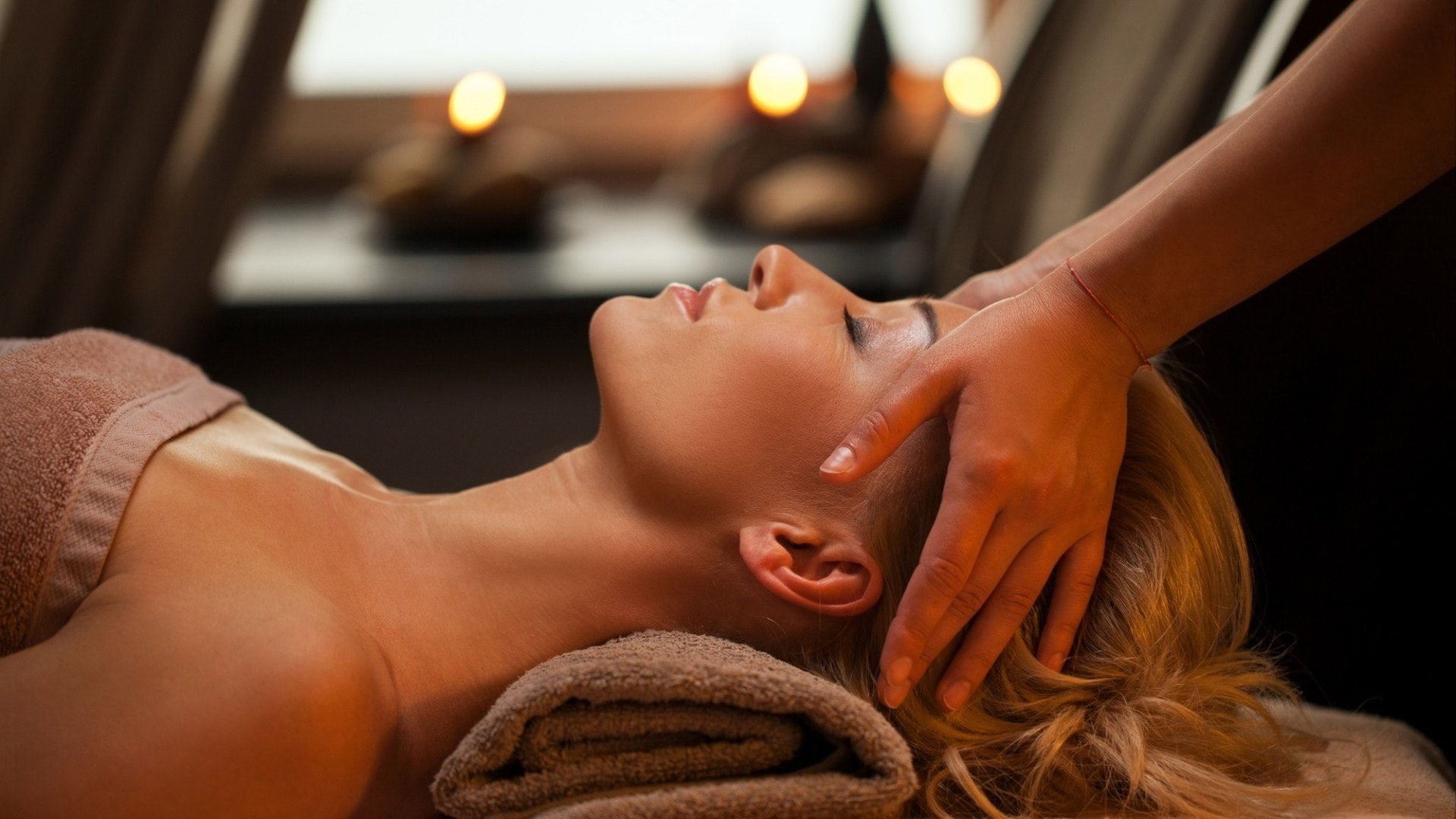 Beautiful young woman enjoys massage in luxury spa