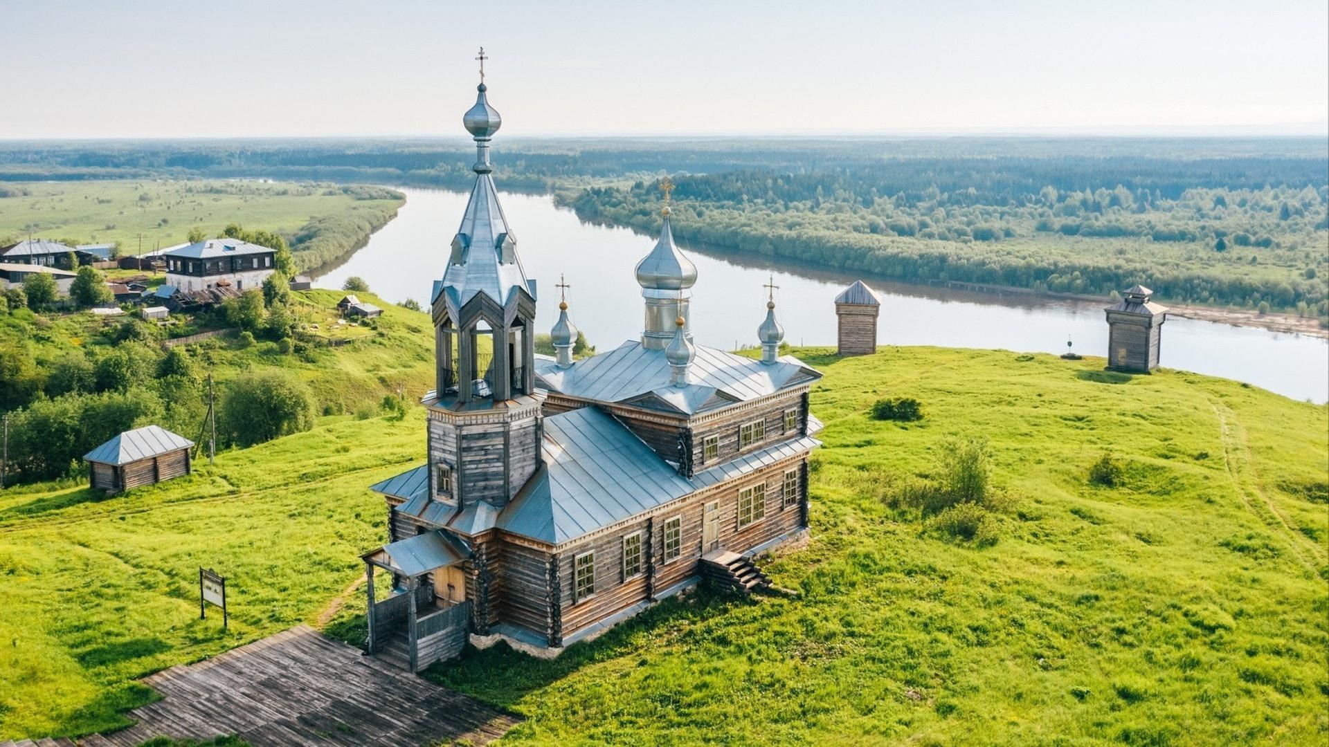 Igreja ortodoxa russa antiga feita de madeira no topo da colina perto do rio na aldeia de Cherdyn, vista aérea