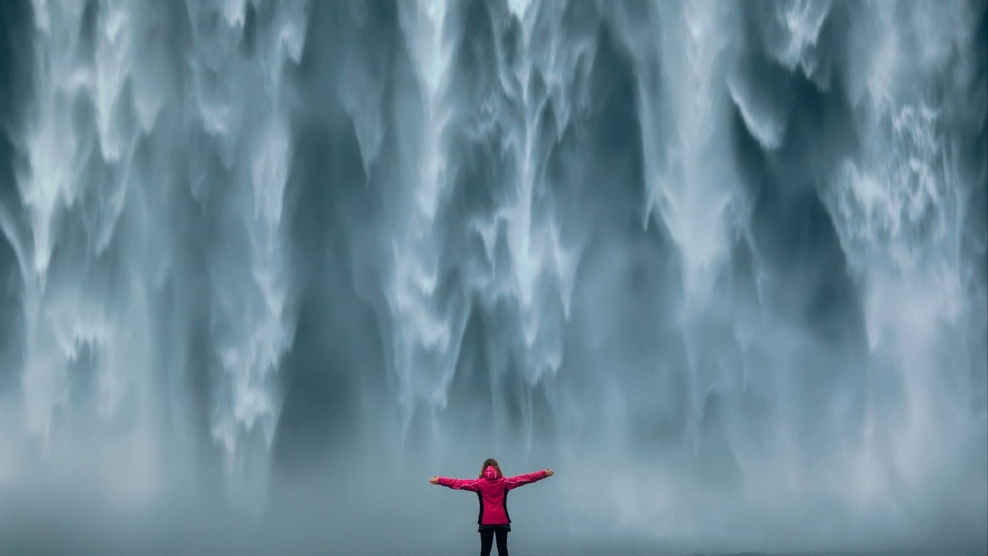 Fille courageuse qui se tenait fièrement debout avec ses bras levés devant le mur d'eau de puissante chute d'eau.