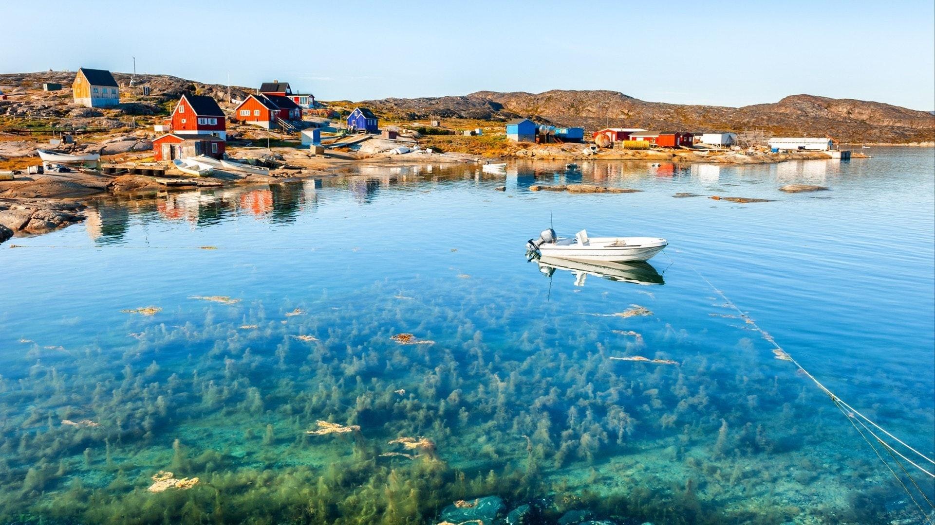 Beautiful sea coast and colourful houses on the rocks in Oqaatsut village