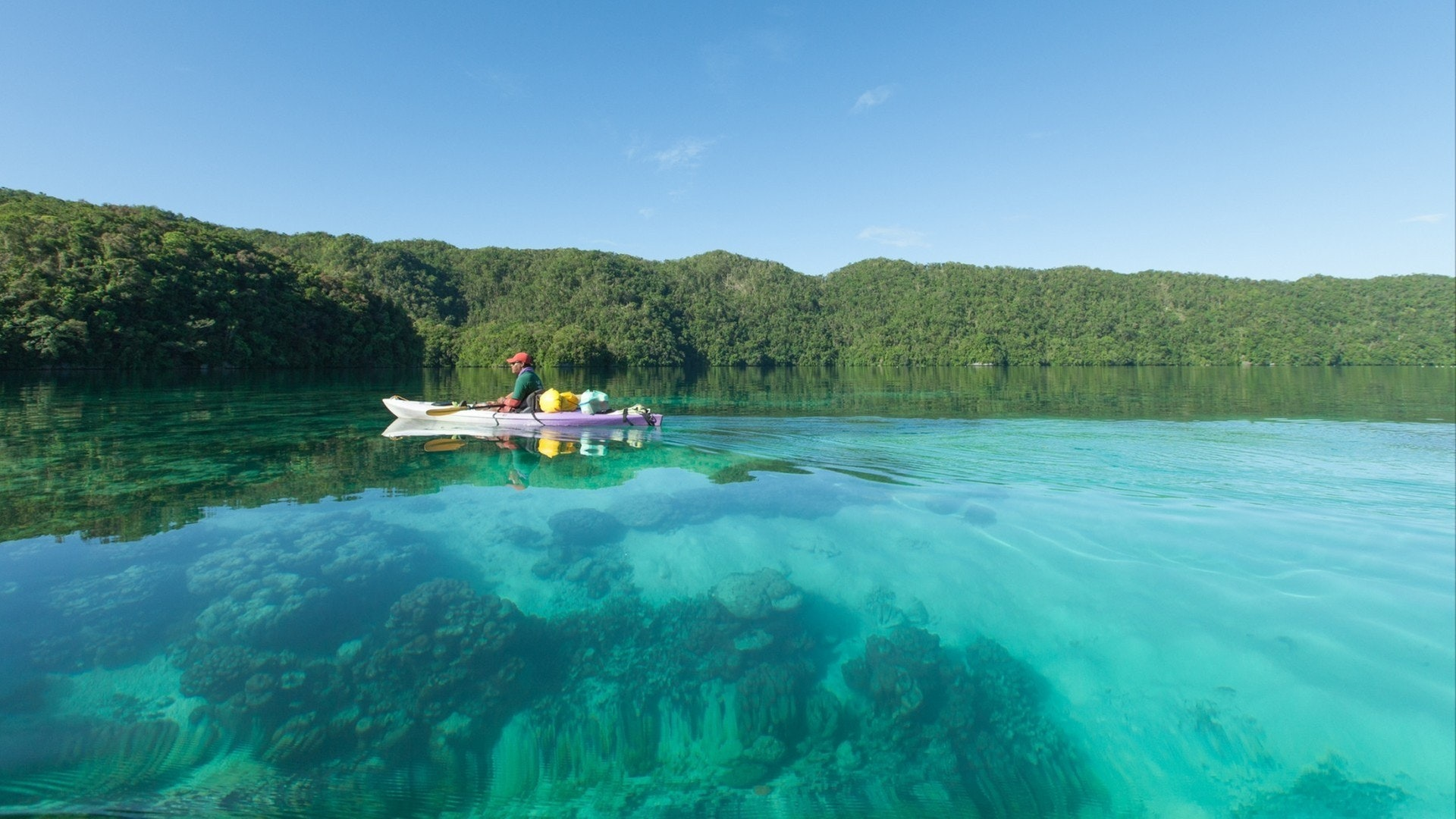 Man paddling his kayak on clear turquoise water of a tropical lagoon
