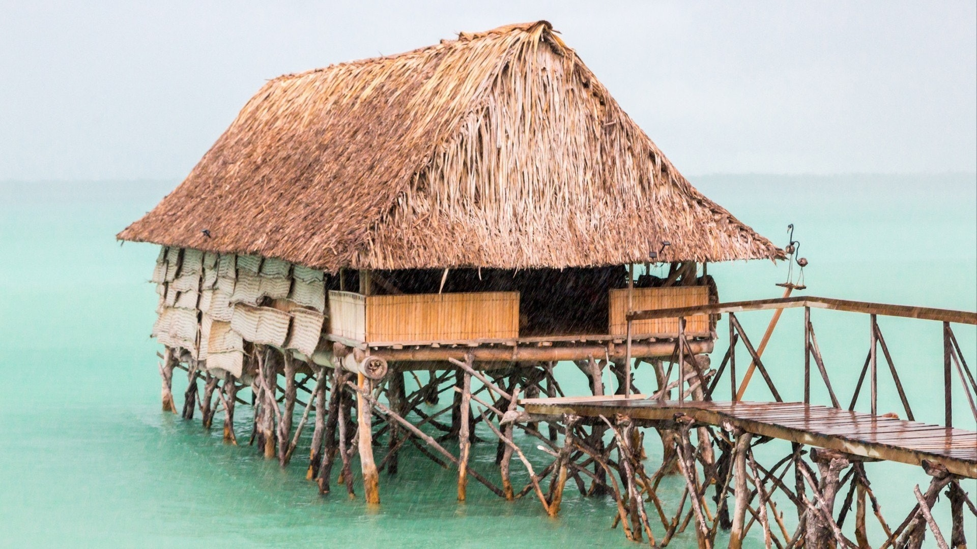 Traditional authentic over water thatched roof bungalow of native local aborigines Micronesian people