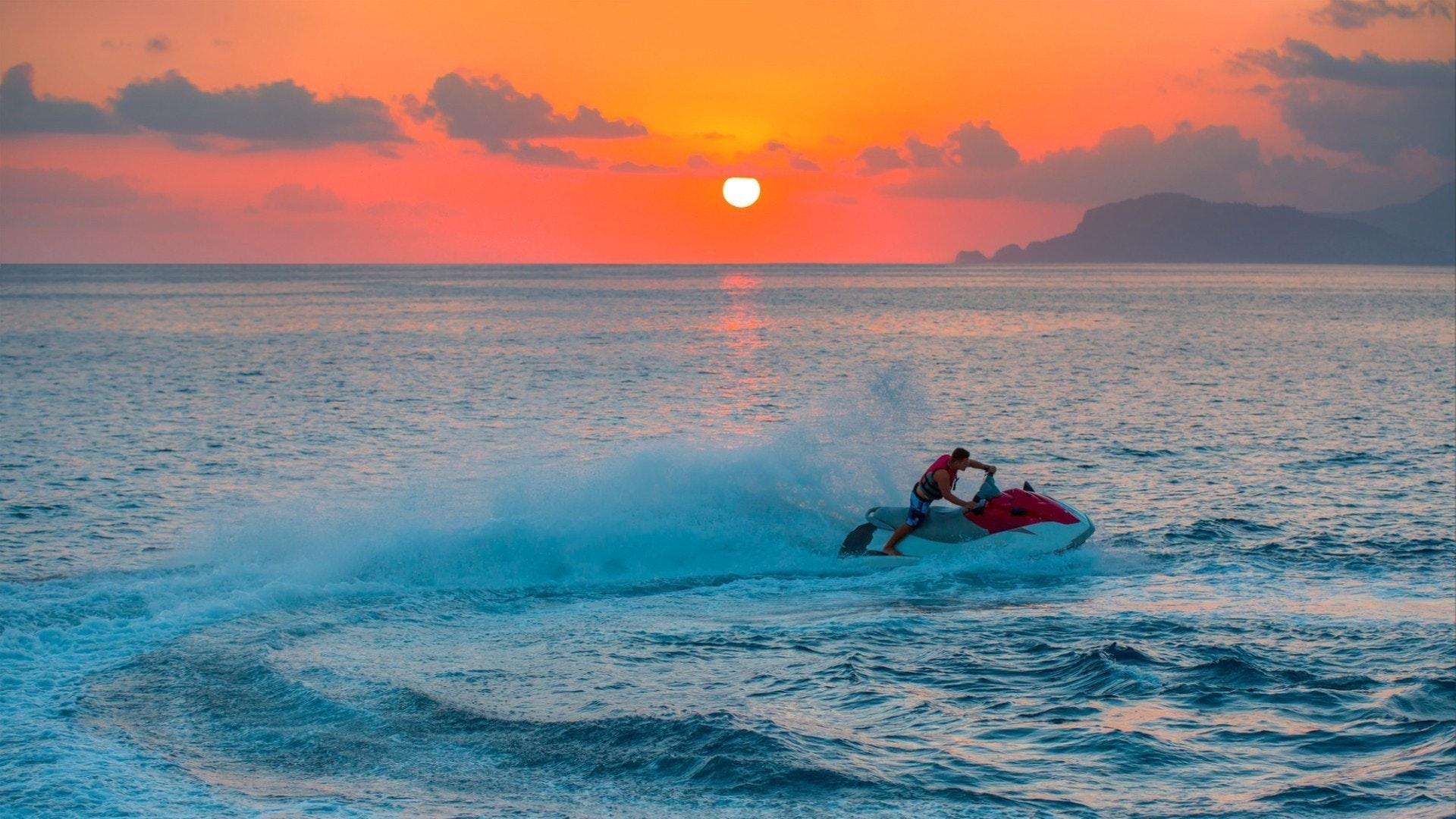 Homem em jetski salto na onda ao pôr do sol, Alanya Turquia
