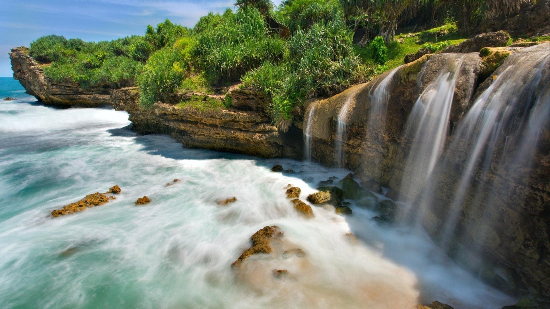Beautiful Jogan waterfall falling to the ocean, Java, Indonesia